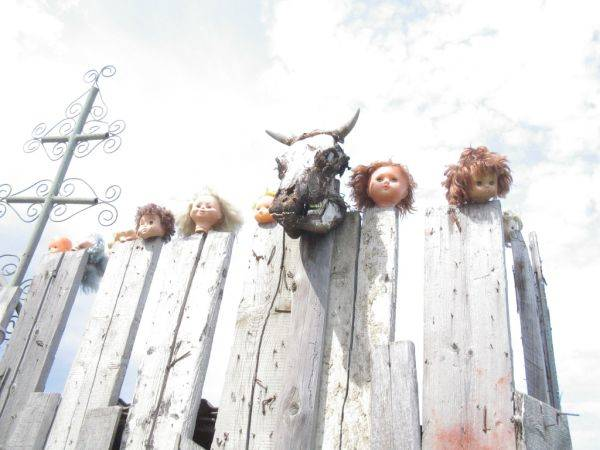 Then you notice something strange on the fence around the property. Something creepy and foreboding. An animal's skull, surrounded by the heads of baby dolls, rests on top of a rotten wooden fence.