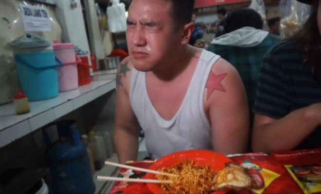 Video grab of Ben Sumadiwiria's facial reaction after taking a bite of the worlds hottest noodles. See SWNS story SWHOT; This is the hilarious moment a man eats the world's hottest noodles - 4,000 times stronger than Tabasco sauce. Ben Sumadiwiria, 22, from London, found the dish at a tiny back street restaurant in Jakarta, Indonesia. The 'death noodles' have 100 bird's eye chilies crushed together giving it a Scoville rating of 20 million - compared with hot Tabasco which is just 5,000 on the scale. Ben scoffed the noodles and started sweating, became dizzy, had to soak his head in water and even went DEAF for two minutes. The chef said: ''This was definitely the hottest thing I've ever eaten. Within seconds of tasting them I was sweating and feeling sick.